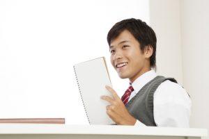 ノートを手に笑顔の男子学生
